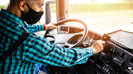 Man wearing mask while driving a truck